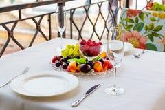 Το πιάτο των φρούτων με τα σμέουρα, τα σταφύλια και τα δαμάσκηνα είναι στον πίνακα για δύο Στοκ Φωτογραφίες