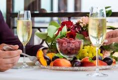 Το πιάτο των φρούτων με τα σμέουρα, τα σταφύλια και τα δαμάσκηνα είναι στον πίνακα για δύο κλείστε επάνω Στοκ Εικόνα