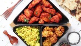 Το πικάντικο ινδικό τηγανισμένο κοτόπουλο εξυπηρέτησε με το φυτικό ρύζι κάρρυ, bhajia κρεμμυδιών, naan ψωμί απόθεμα βίντεο