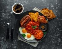 Το πλήρες αγγλικό πρόγευμα με το μπέϊκον, λουκάνικο, τηγάνισε το αυγό, ψημένα φασόλια, hash - Browns και μανιτάρια στο μαύρο πιάτ Στοκ εικόνα με δικαίωμα ελεύθερης χρήσης