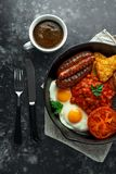 Το πλήρες αγγλικό πρόγευμα με το μπέϊκον, λουκάνικο, τηγάνισε το αυγό, ψημένα φασόλια, hash - Browns και μανιτάρια στο αγροτικό s Στοκ Εικόνες
