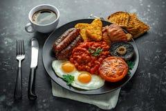 Το πλήρες αγγλικό πρόγευμα με το μπέϊκον, λουκάνικο, τηγάνισε το αυγό, ψημένα φασόλια, hash - Browns και μανιτάρια στο μαύρο πιάτ Στοκ Εικόνα