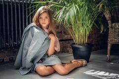 Το πλήρες πορτρέτο σωμάτων ενός κοριτσιού κάθεται σε ένα πάτωμα στοκ εικόνα