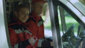 Το πλήρωμα ασθενοφόρων που παρουσιάζει αντίχειρες, επαγγελματίες στο καθήκον παρέχει τις πρώτες βοήθειες απόθεμα βίντεο