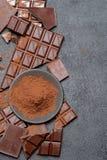 Το πλαίσιο ή τα σύνορα φιαγμένο από οργανικά κομμάτια και κακάο σοκολάτας σκοταδιού ή γάλακτος κονιοποιεί στο σκοτεινό συγκεκριμέ στοκ εικόνα