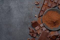 Το πλαίσιο ή τα σύνορα φιαγμένο από οργανικά κομμάτια και κακάο σοκολάτας σκοταδιού ή γάλακτος κονιοποιεί στο σκοτεινό συγκεκριμέ στοκ εικόνες