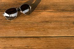 Το πλαίσιο αγκίδων γυαλιών ηλίου είναι στον ξύλινο πίνακα Στοκ εικόνα με δικαίωμα ελεύθερης χρήσης