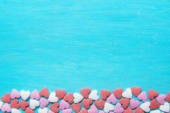 Το πλαίσιο συνόρων από τη ζωηρόχρωμη ζάχαρη ψεκάζει τις καραμέλες που διασκορπίζονται στο ανοικτό μπλε υπόβαθρο Ρομαντική φιλανθρ Στοκ Φωτογραφία