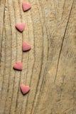 Το πλαίσιο συνόρων από τη ρόδινη ζάχαρη ψεκάζει τις καραμέλες που διασκορπίζονται στο ξεπερασμένο ξύλινο υπόβαθρο Ρομαντική φιλαν Στοκ Φωτογραφίες