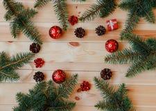 Το πλαίσιο Χριστουγέννων φιαγμένο από κλάδους έλατου, κώνοι πεύκων, δώρο υποκύπτει και κόκκινες σφαίρες στοκ φωτογραφία