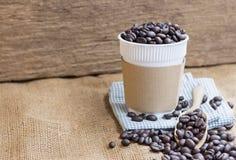 Το πλαστικό φλυτζάνι καφέ με το μανίκι χαρτονιού και ένας σωρός του καφέ είναι Στοκ φωτογραφία με δικαίωμα ελεύθερης χρήσης