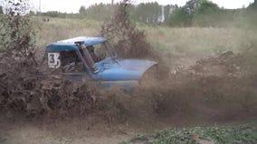 Το πλαϊνό αυτοκίνητο στη φυλή οδηγεί τον ανήφορο από τη βαθιά λάσπη με το νερό Βρώμικος ανταγωνισμός στον ετήσιο αγώνα αυτοκινήτω απόθεμα βίντεο