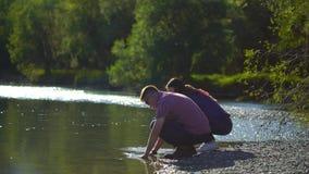 Το πλύσιμο νεαρών άνδρων και γυναικών παραδίδει τον ποταμό και τον ψεκασμό βουνών στο υπόβαθρο των βουνών 4 Κ απόθεμα βίντεο