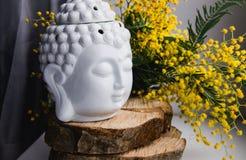 Το πνευματικό τελετουργικό πρόσωπο περισυλλογής του Βούδα στο ξύλο, εγχώριο ντεκόρ, κίτρινο ελατήριο mimosa ανθίζει στοκ φωτογραφία