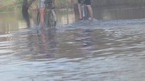 Το ποδήλατο καταβρέχει το νερό γουρνών σε έναν εν μέρει πλημμυρισμένο δρόμο απόθεμα βίντεο