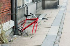Το ποδήλατο παραμένει δεμένο σε έναν σωλήνα αποχέτευσης σε μια εγκαταλειμμένη οδό στοκ εικόνα