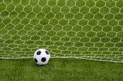 Το ποδόσφαιρο ποδοσφαίρου με το δίχτυ στο τεχνητό πράσινο γήπεδο ποδοσφαίρου χλόης Στοκ Εικόνα