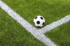 Το ποδόσφαιρο ποδοσφαίρου στην άσπρη γραμμή στον τεχνητό πράσινο τομέα χλόης Στοκ φωτογραφία με δικαίωμα ελεύθερης χρήσης