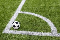 Το ποδόσφαιρο ποδοσφαίρου στη γωνία στον τεχνητό πράσινο τομέα χλόης Στοκ φωτογραφίες με δικαίωμα ελεύθερης χρήσης
