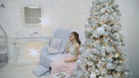 Το πολύ όμορφο κορίτσι πίνει τη σαμπάνια και κάθεται στον καναπέ στο ντεκόρ του νέου έτους φιλμ μικρού μήκους