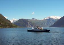 Το πορθμείο πλέει πέρα από το φιορδ Υπόβαθρο βουνών Στοκ Φωτογραφίες