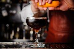 Το πορτοκάλι διακοσμεί τον ψεκασμό πέρα από ένα ποτό Στοκ Εικόνες