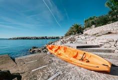 Το πορτοκαλί καγιάκ είναι στην αποβάθρα θάλασσας, αδριατική παραλία OD Κροατία Στοκ Φωτογραφία
