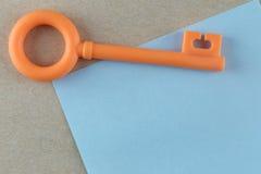 Το πορτοκαλί πλαστικό κλειδί τοποθετείται στην μπλε σημείωση εγγράφου Στοκ Φωτογραφία