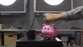 Το πορτοφόλι και η piggy τράπεζα τίθενται στον πίνακα, το χέρι του αρσενικού παρουσιάζει αντίχειρα πέρα από τους απόθεμα βίντεο