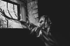 Το πορτρέτο ένας ασθενής γυναικών ` s τραβά τα χέρια της στο φως στο παράθυρο ενός ψυχιατρείου Στοκ Φωτογραφίες