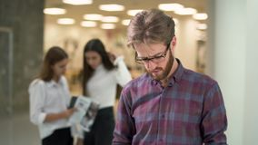 Το πορτρέτο ένας τύπος με μια γενειάδα στα γυαλιά και την περιστασιακή ανάγνωση πουκάμισων καρό τεκμηριώνει με τις πωλήσεις τις ε απόθεμα βίντεο