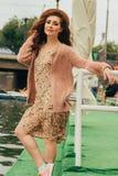 Το πορτρέτο ένα όμορφο και ελκυστικό κορίτσι, γυναίκες στέκεται κοντά στο κιγκλίδωμα και τις βάρκες, στον ποταμό θέτει στοκ φωτογραφία με δικαίωμα ελεύθερης χρήσης