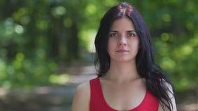 Το πορτρέτο γυναικών στο δασικό, όμορφο θηλυκό στο κόκκινο κοιτάζει, τοποθετεί για το κείμενο αγγελιών, αργό απόθεμα βίντεο
