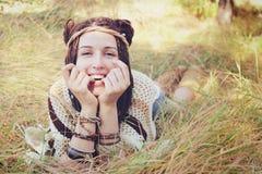 Το πορτρέτο γυναικών χαμόγελου ύφους Boho, κορίτσι έχει μια διασκέδαση που βρίσκεται υπαίθρια στο ηλιόλουστο πάρκο φθινοπώρου Στοκ Εικόνες
