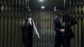 Το πορτρέτο δύο άτομα γκάγκστερ στα επίσημα κοστούμια και το καπέλο fedora που ανοίγουν ένα μέταλλο σφυρηλάτησε τις πύλες φιλμ μικρού μήκους