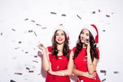 Το πορτρέτο δύο ευτυχών νέων γυναικών στο κόκκινο ντύνει και του καπέλου santa στο κομφετί κομμάτων πέρα από το άσπρο υπόβαθρο Νέ στοκ φωτογραφία