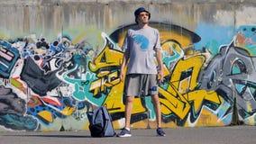 Το πορτρέτο ενός αρσενικού καλλιτέχνη στέκεται στην οδό με ένα γκράφιτι χρωματίζοντας στο υπόβαθρο απόθεμα βίντεο