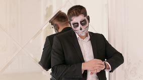 Το πορτρέτο ενός ατόμου με ένα κρανίο makeup έντυσε σε ένα κοστούμι, ενάντια στον τοίχο καθρεφτών φιλμ μικρού μήκους