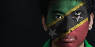 Το πορτρέτο ενός ατόμου με τη σημαία των Σαιντ Κιτς και Νέβις χρωμάτισε στο πρόσωπό του στο μαύρο υπόβαθρο στοκ φωτογραφίες