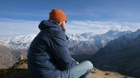 Το πορτρέτο ενός γενειοφόρου ταξιδιώτη στα γυαλιά ηλίου και μια ΚΑΠ κάθεται σε έναν βράχο ενάντια στο σκηνικό των βουνών απόθεμα βίντεο