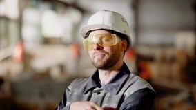 Το πορτρέτο ενός ενήλικου εργάτη οικοδομών σε ένα προστατευτικό κράνος, ένα πρόσωπο απολαμβάνει τη διαδικασία την υψηλή ποιότητα φιλμ μικρού μήκους