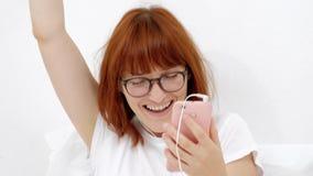 Το πορτρέτο ενός κοριτσιού με ένα τηλέφωνο, βρίσκει η συμπάθειά ότι σας συντονίζει σε ένα έξυπνο τηλέφωνο χαμογελώντας, ακούει το απόθεμα βίντεο