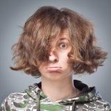 Το πορτρέτο ενός κοριτσιού με την ατημέλητη τρίχα, συγκινήσεις δροσίζει στο στούντιο στο γκρίζο υπόβαθρο Στοκ Εικόνες