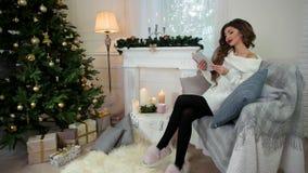Το πορτρέτο ενός κοριτσιού που διαβάζει ένα βιβλίο, πίνοντας το τσάι, καθμένος στον καναπέ, γυναίκα που φορά ένα θερμό πλεκτό που απόθεμα βίντεο