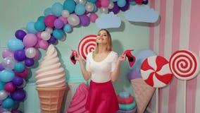 Το πορτρέτο ενός κοριτσιού που κρατά τα ρόδινα παπούτσια σε την παραδίδει το στούντιο με τα τεράστια γλυκά φιλμ μικρού μήκους