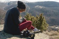 Το πορτρέτο ενός κοριτσιού φωτογράφων σχεδιαστών hipster στο καπέλο και τα γυαλιά ηλίου επισύρει την προσοχή μια κρητιδογραφία στ στοκ εικόνες