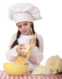 Το πορτρέτο ενός μικρού κοριτσιού σε μια άσπρη ποδιά και το καπέλο αρχιμαγείρων τεμαχίζουν το γ Στοκ εικόνα με δικαίωμα ελεύθερης χρήσης