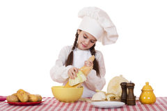 Το πορτρέτο ενός μικρού κοριτσιού σε μια άσπρη ποδιά και το καπέλο αρχιμαγείρων τεμαχίζουν το γ Στοκ Φωτογραφίες