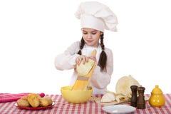 Το πορτρέτο ενός μικρού κοριτσιού σε μια άσπρη ποδιά και το καπέλο αρχιμαγείρων τεμαχίζουν το γ Στοκ Εικόνα