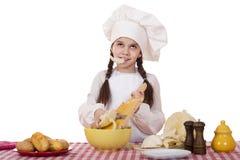 Το πορτρέτο ενός μικρού κοριτσιού σε μια άσπρη ποδιά και το καπέλο αρχιμαγείρων τεμαχίζουν το γ Στοκ Εικόνες